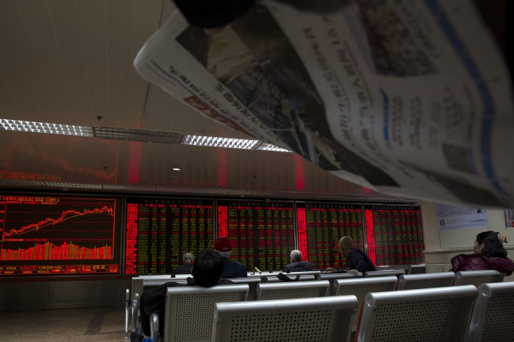Investors monitor stock prices near a display in Beijing Monday, Nov. 27, 2017. Asian stock markets tumbled Monday as investors looked ahead to a possible U.S. Senate vote this week on proposed tax changes and a week of economic data announcements. (AP Photo/Ng Han Guan)