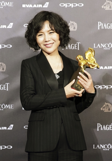 """Chinese director Vivian Qu holds her awards and poses for media for Best The Best Director at the 54th Golden Horse Awards in Taipei, Taiwan, Saturday, Nov. 25, 2017. Qu won for the film """"Angels Wear White"""" at this year's Golden Horse Awards -the Chinese-language film industry's biggest annual events.(AP Photo/ Billy Dai)"""