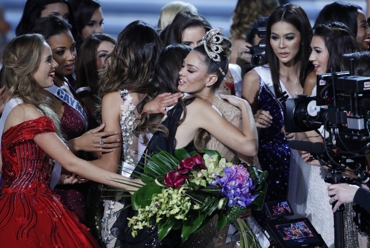 Contestants embrace new Miss Universe Miss South Africa Demi-Leigh Nel-Peters, in crown, at the Miss Universe pageant Sunday, Nov. 26, 2017, in Las Vegas. (AP Photo/John Locher)