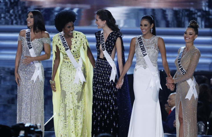 From left, final five finalists Miss Colombia Laura Gonzalez, Miss Jamaica Davina Bennett, Miss Thailand Maria Poonlertlarp, Miss Venezuela Keysi Sayago and Miss South Africa Demi-Leigh Nel-Peters stand on stage at the Miss Universe pageant Sunday, Nov. 26, 2017, in Las Vegas. (AP Photo/John Locher)