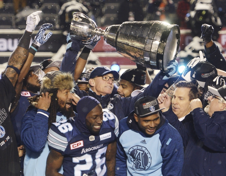 Toronto Argonauts head coach Marc Trestman, center, and players celebrate with the Grey Cup after defeating the Calgary Stampeders in the Grey Cup CFL football game in Ottawa on Sunday, Nov. 26, 2017. The Argonauts won, 27-24. (Ryan Remiorz/The Canadian Press via AP)