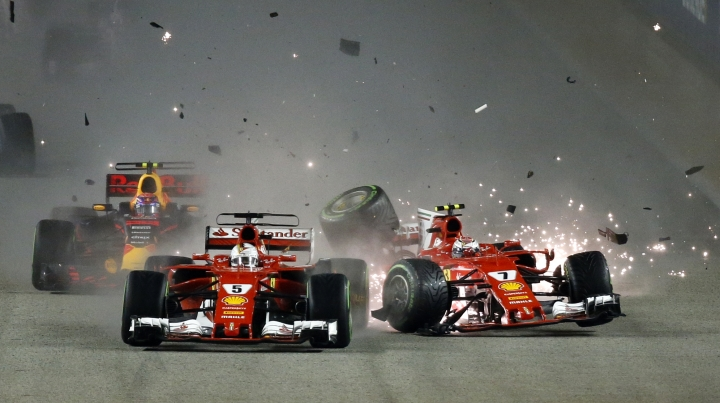 FILE - This is a Sunday, Sept. 17, 2017 file photo of Ferrari driver Kimi Raikkonen, right, of Finland colliding with teammate Sebastian Vettel of Germany at the start of the Singapore Formula One Grand Prix on the Marina Bay City Circuit Singapore. Ferrari driver Sebastian Vettel must cope better under pressure if he wants to wrestle the Formula One title back from Lewis Hamilton next year. (AP Photo/ Yong Teck Lim, File)