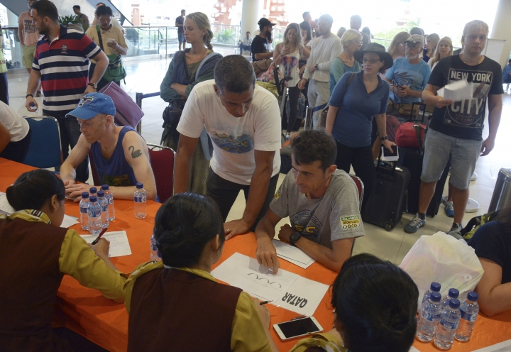 Passengers talk to ground crew as their flights are cancelled at Ngurah Rai International Airport in Bali, Indonesia, Tuesday, Nov. 28, 2017. Indonesia's disaster mitigation agency says the airport on the tourist island of Bali is closed for a second day due to the threat from volcanic ash. (AP Photo/Ketut Nataan)