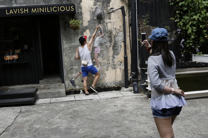 In this Sunday, Nov. 12, 2017, photo, a tourist takes a photo of a friend pretending to play basketball with characters depicted on a George Town street art mural on the island of Penang, Malaysia. George Town oozes a hauntingly rustic charm, with colorful street art as much a draw as the historical architecture and one of Southeast Asia's tastiest street food scenes. (AP Photo/Adam Schreck)