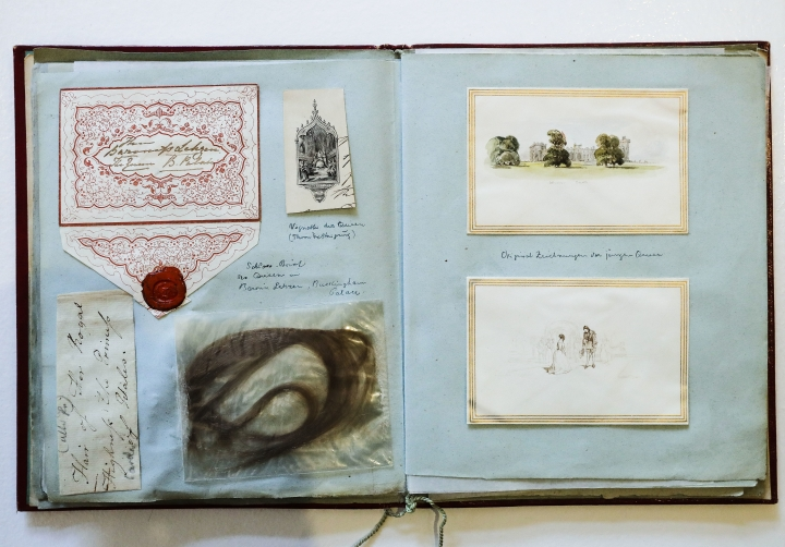 In this Nov. 28, 2017 photo, a letter, drawings and a ringlet fixed in a scrapbook with items belonging to Britain's former Queen Victoria in Berlin, Germany. The scrapbook is displayed at Grisebach auctioneers and will be offered at an auction in Berlin on Thursday, Nov. 30, 2017. (AP Photo/Markus Schreiber)