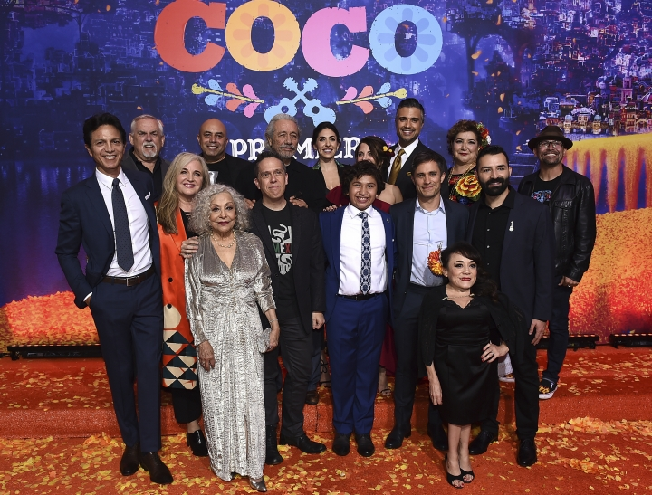 "FILE - In this Nov. 8, 2017 file photo, the cast and filmmakers, from left, Benjamin Bratt, John Ratzenberger, Darla K. Anderson, Renee Victor, Herbert Siguenza, Lee Unkrich, Edward James Olmos, Natalia Cordova-Buckley, Anthony Gonzalez, Alanna Ubach, Jaime Camil, Gael Garcia Bernal, Selene Luna, Blanca Araceli, Adrian Molina and Lombardo Boyar arrive at the Los Angeles premiere of ""Coco"" in Los Angeles. The film is one of the largest U.S. productions ever to feature an almost entirely Latino cast and is drawing large audiences among Latinos, offering a momentary relief to some anxious about uncertain immigration policies. (Photo by Jordan Strauss/Invision/AP)"