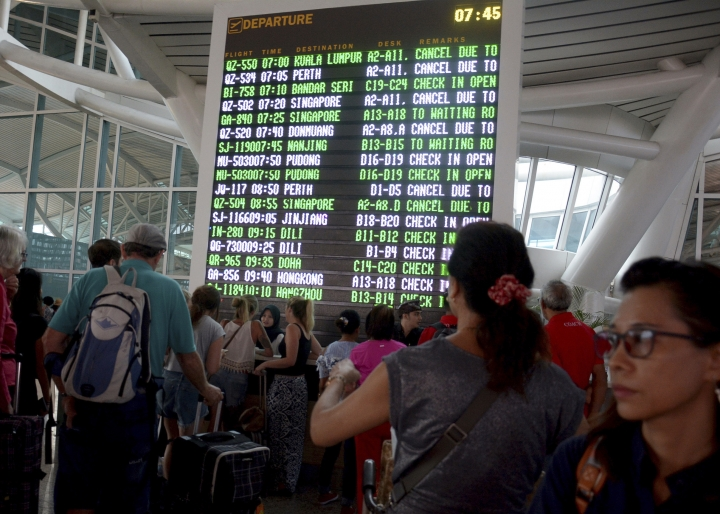 FILE - In this Monday, Nov. 27, 2017, file photo, a flight information board shows cancelled flights due to smoke from Mount Agung at the Ngurah Rai International Airport in Bali, Indonesia. Australia's prime minister says he is discussing with his government how to help thousands of Australian holidaymakers stranded by volcanic smoke on the Indonesian resort island of Bali. (AP Photo/Ketut Nataan, File)
