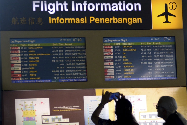 A foreign tourist uses her mobile phone to take pictures of a flight information board showing cancelled flights at Ngurah Rai International Airport in Bali, Indonesia, Wednesday, Nov. 29, 2017. Mount Agung, a volcano with a deadly history continued to erupt on the popular resort island, stranding tens of thousands of tourists as authorities extended the closure of the airport due to concerns that jet engines could choke on the thick volcanic ash from the eruption which was moving across the island. (AP Photo/Ketut Nataan)
