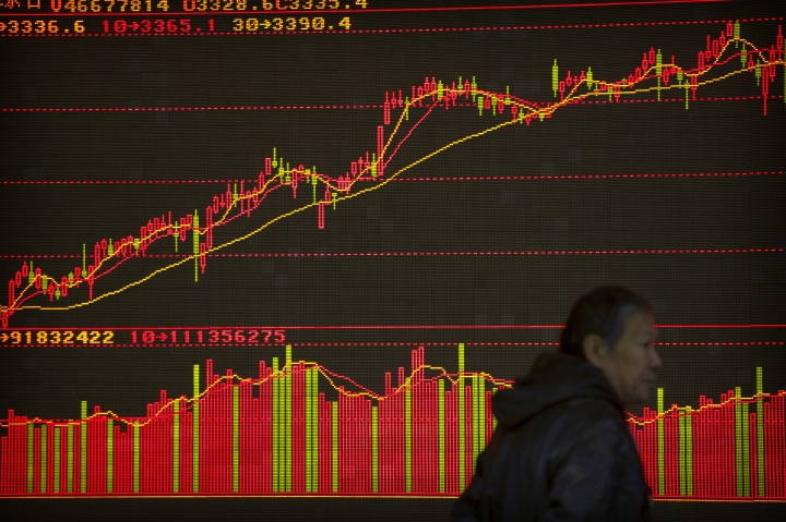 A Chinese investor walks past a display showing stock information at a brokerage house in Beijing, Thursday, Nov. 30, 2017. Asian stock markets declined Thursday after U.S. tech stocks fell and China reported stronger manufacturing as investors looked ahead to a key OPEC meeting. (AP Photo/Mark Schiefelbein)