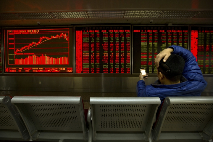 A Chinese investor looks at his smartphone as he monitors stock prices at a brokerage house in Beijing, Thursday, Nov. 30, 2017. Asian stock markets declined Thursday after U.S. tech stocks fell and China reported stronger manufacturing as investors looked ahead to a key OPEC meeting. (AP Photo/Mark Schiefelbein)