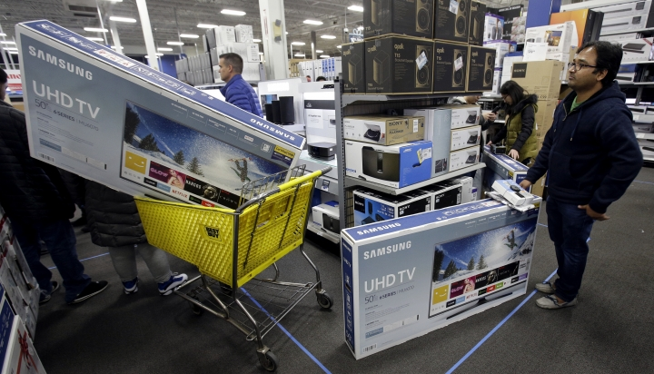 FILE - In this Thursday, Nov. 23, 2017, file photo, people wait to pay for televisions as they shop a sale at a Best Buy store on Thanksgiving Day, in Overland Park, Kan. For the five-day period that ended the Monday after Thanksgiving, shoppers seemed to spend more in 2017 compared to a year earlier. (AP Photo/Charlie Riedel, File)