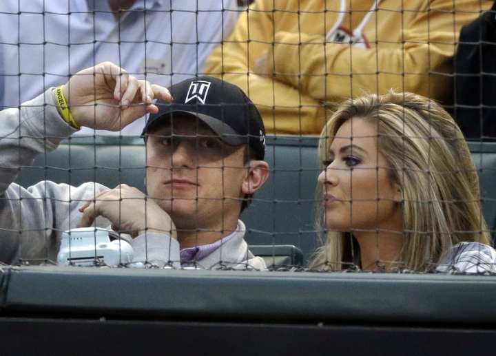 FILE - In this April 14, 2015, file photo, Cleveland Browns quarterback Johnny Manziel, left, sits with Colleen Crowley during a baseball game between the Los Angeles Angels and the Texas Rangers in Arlington, Texas. Prosecutors in Dallas have dismissed a 2016 misdemeanor domestic assault charge against Heisman Trophy-winning quarterback Johnny Manziel. The Dallas County District Attorney's Office on Thursday, Nov. 30, 2017, confirmed Manziel successfully completed requirements of a court agreement that included taking an anger management course and participating in the NFL's substance abuse program. The 24-year-old Manziel also had to stay away from Colleen Crowley, who accused him of hitting and threatening her during a January 2016 night out. (AP Photo/LM Otero, File)