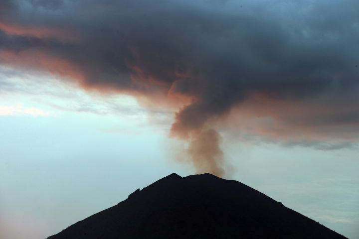 A view of Mount Agung volcano erupting during a sunset in Karangasem, Bali, Indonesia, Thursday, Nov. 30, 2017. Authorities have told tens of thousands of people to leave an area extending 10 kilometers (6 miles) from the volcano as it belches volcanic materials into the air. Mount Agung's last major eruption in 1963 killed about 1,100 people. (AP Photo/Firdia Lisnawati)