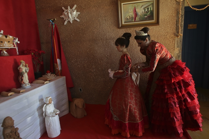 In this Nov. 12, 2017 photo, Luana Borges, right, adjusts her daughter Luana Silva's red dress, as they dress up as Portuguese royalty for the Azorean Culture Festival, which celebrates the culture of the Azores, the Portuguese island chain that lies in the mid-Atlantic, in Enseada de Brito, in Brazil's Santa Catarina southern state. At the climax of the festival, a couple that represents the Portuguese emperor and his wife lead a parade of attendants for a church Mass. (AP Photo/Eraldo Peres)