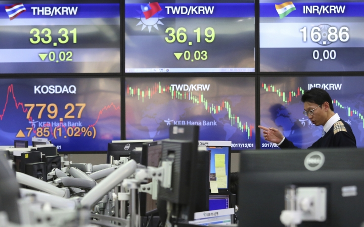A currency trader works at the foreign exchange dealing room of the KEB Hana Bank headquarters in Seoul, South Korea, Friday, Dec. 1, 2017. Asian stock markets were marginally higher Friday, after an overnight recovery of technology stocks on Wall Street. An agreement among key crude exporting countries to extend oil output cuts boosted sentiment. (AP Photo/Ahn Young-joon)