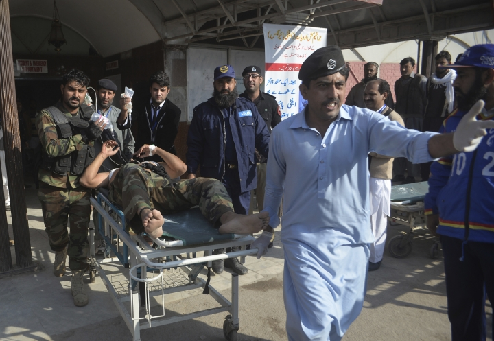 Staff rush Pakistani security personnel injured to hospital during a crackdown operation against militants who stormed the agriculture institute in Peshawar, Pakistan, Friday, Dec. 1, 2017. Pakistani police say gunmen have stormed a government complex in the northwestern city of Peshawar, killing an unconfirmed number of people. (AP Photo/Muhammad Sajjad)