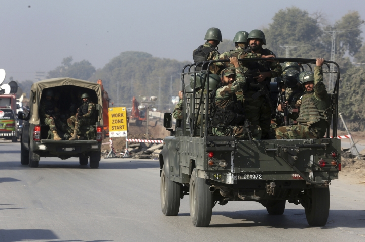 Pakistani troops rush to the agriculture institute stormed by militants in Peshawar, Pakistan, Friday, Dec. 1, 2017. Pakistani police say gunmen have stormed a government complex in the northwestern city of Peshawar, killing an unconfirmed number of people. (AP Photo/Muhammad Sajjad)