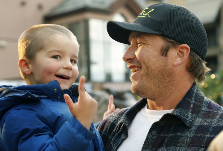 In this Friday, Dec. 1, 2017 photo, Bode Miller holds his son Nate after a news conference in Beaver Creek, Colo. Miller's ambition now is to be just as entertaining as a ski racing analyst as he was when he competed. He will work for NBC at the Pyeongchang Olympics. (AP Photo/Nathan Bilow)