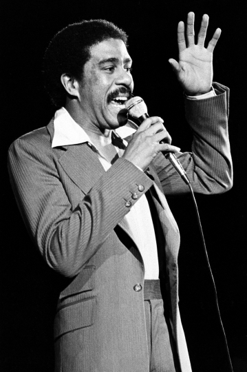 FILE - In this 1977 file photo comedian-actor Richard Pryor is shown as he performs. Pryor, a fledgling stand-up comedian who had been playing small coffeehouses, helped the Improv establish itself when he became one of the first comics to take to its stage soon after it opened in New York in 1963. (AP Photo,File)