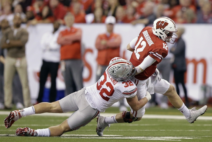Wisconsin quarterback Alex Hornibrook (12) is tackled by Ohio State's Tuf Borland (32) during the first half of the Big Ten championship NCAA college football game, Saturday, Dec. 2, 2017, in Indianapolis. (AP Photo/AJ Mast)