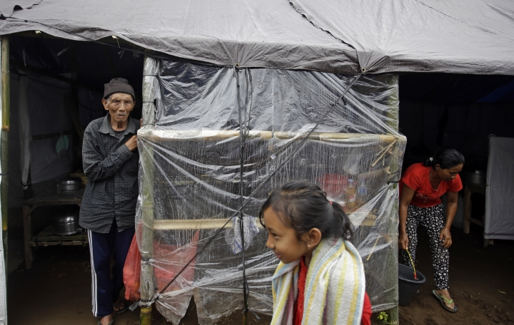Villagers stay at a temporary shelter following the eruption of Mount Agung in Karangasem, Bali, Indonesia, Saturday, Dec. 2, 2017. Bali's glowering Mount Agung has seemingly quietened since hurling huge columns of ash from its crater a week ago but some villagers who survived its catastrophic 1963 explosions say they believe a bigger eruption is coming. Explosions from the smoking crater and tremors still rattle the surrounding region and authorities have maintained Agung's alert at the highest level. Its 1963 eruptions killed about 1,100 people. (AP Photo/Firdia Lisnawati)