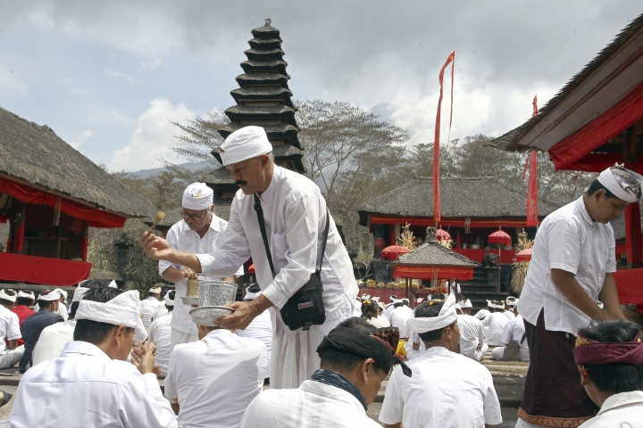 Hindu priests give holy water to worshipers during a prayer at a temple located a few kilometers (miles) from the crater of the Mount Agung volcano in Karangasem, Bali, Indonesia, Sunday, Dec. 3, 2017. Authorities have told tens of thousands of people to leave an area extending 10 kilometers (6 miles) from the volcano as it belches volcanic materials into the air. Mount Agung's last major eruption in 1963 killed about 1,100 people. (AP Photo/Firdia Lisnawati)