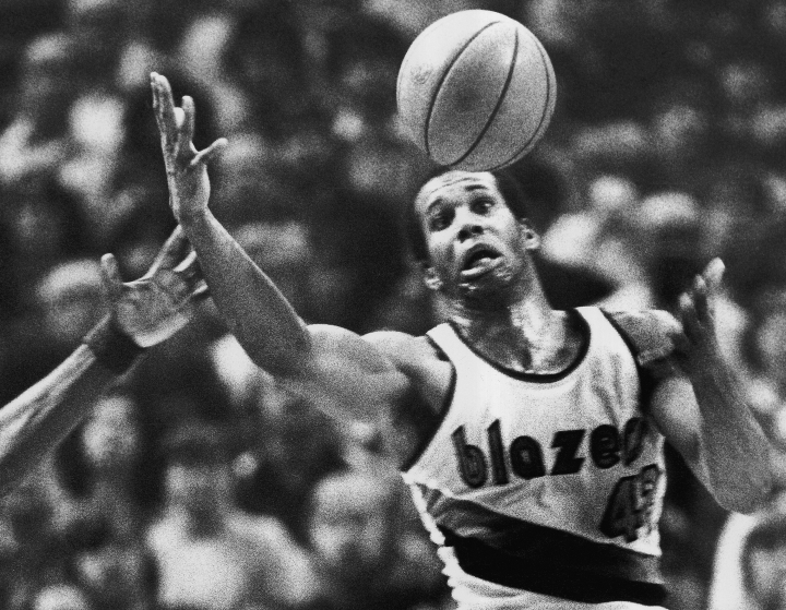 FILE - In this Dec. 25, 1979, file photo, Portland Trail Blazers' Kermit Washington gains control of a loose ball during an NBA basketball game against the Golden State Warriors in Portland, Ore. Washington has pleaded guilty Thursday, Nov. 30, 2017, to spending thousands of dollars donated to an African charity he organized on jewelry, vacations and other personal items. Washington was scheduled to go to trial in federal court Monday, Dec. 4, 2017, in Kansas City, Mo., but instead pleaded guilty Thursday. (AP Photo/Jack Smith, File)