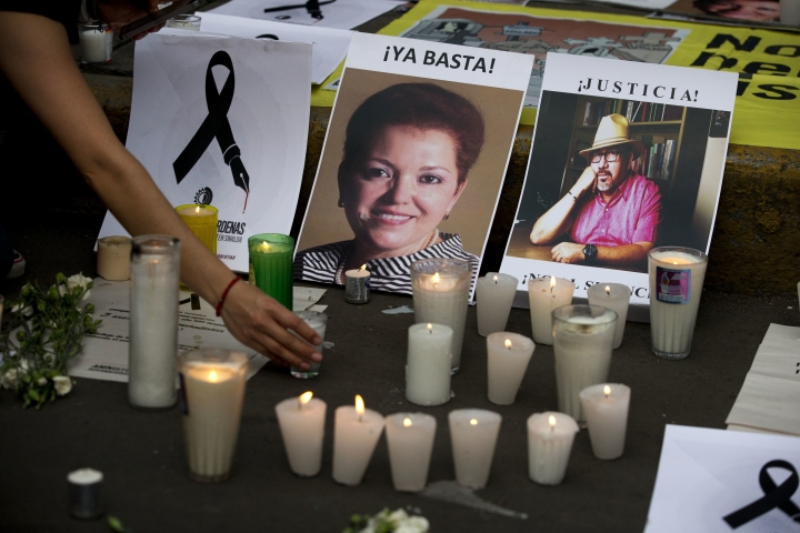 FILE - In this May 16, 2017 file photo, a woman places a candle in front of pictures of murdered journalists Miroslava Breach, left, and Javier Valdez during a demonstration against the killing of journalists, outside the Interior Ministry in Mexico City. More than three dozen Mexican media organizations announced Monday, Dec. 4, 2017 that they are joining forces to try to combat a wave of journalist killings in the country, including at least nine this year. (AP Photo/Rebecca Blackwell, File)
