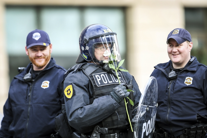 """An officer smells a flower that a protestor gave him after the protest downtown against President Donald Trump during his visit to the State Capital in Salt Lake on Monday, Dec. 4, 2017. Trump on Monday took the rare step of scaling back two sprawling national monuments in Utah, declaring that """"public lands will once again be for public use"""" in a move cheered by Republican leaders who lobbied him to undo protections they considered overly broad. (Adam Fondren/The Deseret News via AP)"""