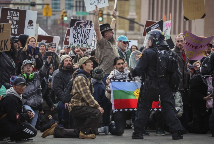 """Protesters kneel in the middle of State Street police try to break up a march through downtown Salt Lake City on Monday, Dec. 4, 2017, in Salt Lake City. Roughly 3,000 demonstrators lined up near the State Capitol to protest President Donald Trump's announcement of scaling back two sprawling national monuments, and his declaring that """"public lands will once again be for public use."""" (Benjamin Zack/Standard-Examiner via AP)"""