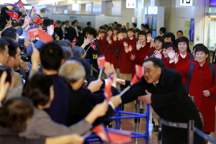 North Korean women's national soccer team members are welcomed with their national flags waved upon arrival at Haneda international airport in Tokyo Tuesday, Dec. 5, 2017. North Korean women's and men's national soccer teams arrived in Tokyo as exception to Japan's entry ban as part of ongoing sanctions against Pyongyang's missile and nuclear development. North Korea is competing against Japan, China and South Korea in the upcoming E-1 Football Championship held in Japan. (AP Photo/Shizuo Kambayashi)