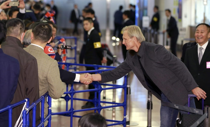 North Korean men's national soccer team head coach Jorn Andersen of Norway is greets by North Korea residents in Japan upon arrival at Haneda international airport in Tokyo Tuesday, Dec. 5, 2017. North Korean women's and men's national soccer teams arrived in Tokyo as exception to Japan's entry ban as part of ongoing sanctions against Pyongyang's missile and nuclear development. North Korea is competing against Japan, China and South Korea in the upcoming E-1 Football Championship held in Japan. (AP Photo/Shizuo Kambayashi)