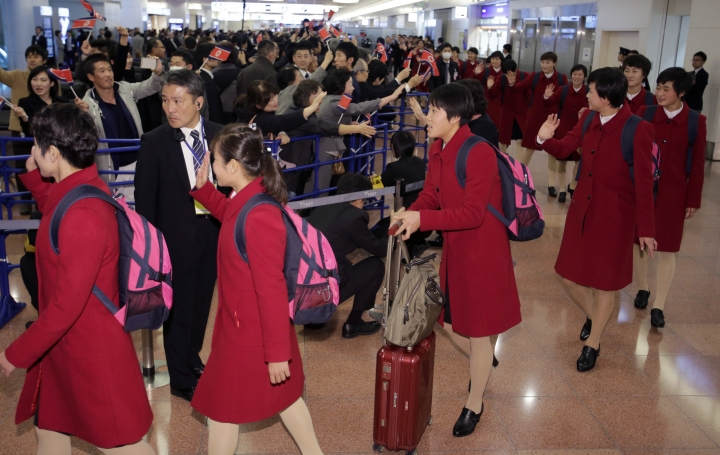 North Korean women's national soccer team members, in red, wave upon arrival at Haneda international airport in Tokyo Tuesday, Dec. 5, 2017. North Korean women's and men's national soccer teams arrived in Tokyo as exception to Japan's entry ban as part of ongoing sanctions against Pyongyang's missile and nuclear development. North Korea is competing against Japan, China and South Korea in the upcoming E-1 Football Championship held in Japan. (AP Photo/Shizuo Kambayashi)