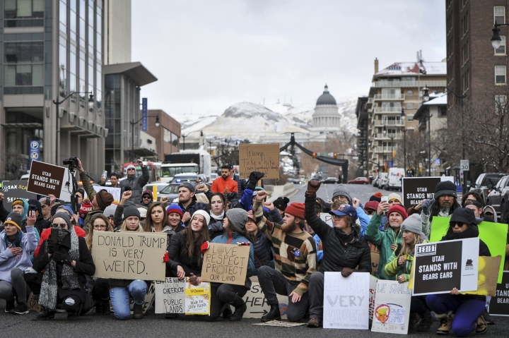 After they took over the intersection of 100S and State Street stopping traffic, the protesters kneel in solidarity during the protest against President Donald Trump during his visit to the State Capital in Salt Lake on Monday, Dec. 4, 2017. (Adam Fondren/The Deseret News via AP)