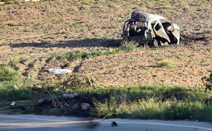 FILE - This Oct. 16, 2017 file photo shows the wreckage of the car of investigative journalist Daphne Caruana Galizia after a car bomb which killed her, next to a road in the town of Mosta, Malta. On Monday, Dec. 4, 2017 Malta's prime minister Joseph Muscat announced the arrest of eight suspects, all Maltese citizens, in the murder of the journalist. (AP Photo/Rene Rossignaud, file)