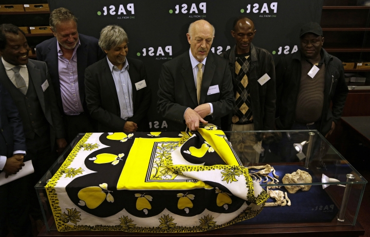 "Ron Clarke, a professor from the Evolutionary Studies Institute at the University of the Witwatersrand, center, unveils the virtually complete Australopithecus fossil ""Little Foot"" in Johannesburg, South Africa, Wednesday, Dec. 6, 2017. Researchers in South Africa have unveiled what they call ""by far the most complete skeleton of a human ancestor older than 1.5 million years ever found."" (AP Photo/Themba Hadebe)"