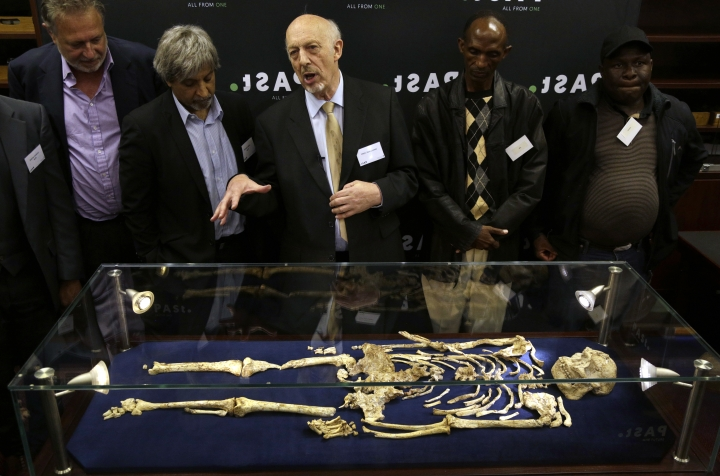 """Ron Clarke, a professor from the Evolutionary Studies Institute at the University of the Witwatersrand, center, speaks during the unveiling of a virtually complete Australopithecus fossil """"Little Foot"""" in Johannesburg, South Africa, Wednesday, Dec. 6, 2017. Researchers in South Africa have unveiled what they call """"by far the most complete skeleton of a human ancestor older than 1.5 million years ever found."""" (AP Photo/Themba Hadebe)"""