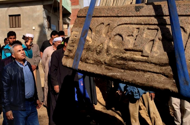 This photo released by the Egyptian Ministry of Antiquities, shows workers moving a gate made of granite dating back nearly 3,000 years from north Cairo to a new museum near the famed pyramids in Giza, in Sharqiya province, Egypt, Wednesday, Dec. 6, 2017. The statement says the gate is made from pink granite and bears royal cartouches referring to Amenemhat I, the first king of the 12th dynasty of ancient Egypt. (Egyptian Ministry of Antiquities via AP)
