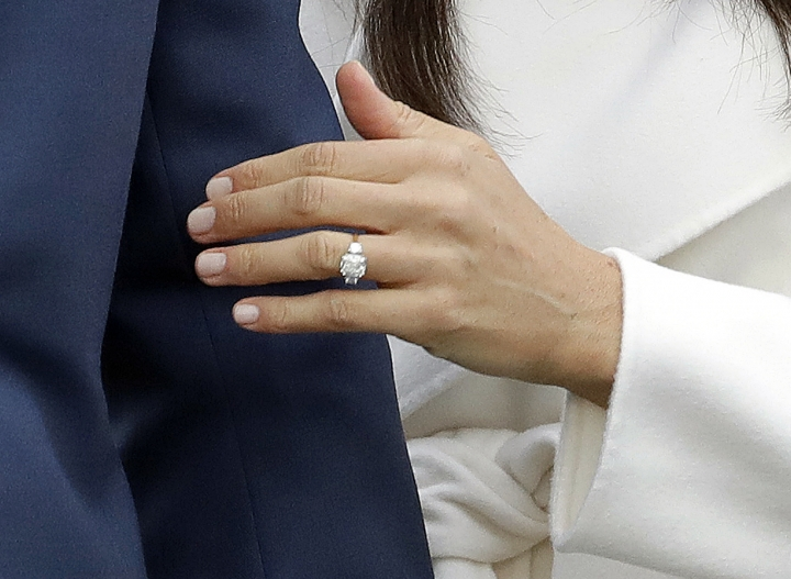 FILE - In this Monday, Nov. 27, 2017 file photo, Britain's Prince Harry's fiancee Meghan Markle shows off her engagement ring as she poses for photographers during a photocall in the grounds of Kensington Palace in London. The jewelry maker who worked on the engagement ring Prince Harry gave to Meghan Markle says it's been inundated with requests for replicas_ but it won't be taking any orders for copycat rings, it was reported on Wednesday, Dec. 6, 2017. (AP Photo/Matt Dunham, File)