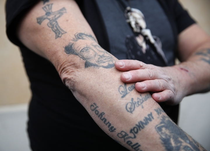 Johnny Hallyday's fan Yves Buisson shows his tattoos outside Hallyday's house in Marnes-la-Coquette, outside Paris, Wednesday, Dec.6, 2017. Johnny Hallyday, France's biggest rock star for more than half a century and an icon who packed sports stadiums and all but lit up the Eiffel Tower with his pumping pelvis and high-voltage tunes, has died. He was 74. (AP Photo/Christophe Ena)