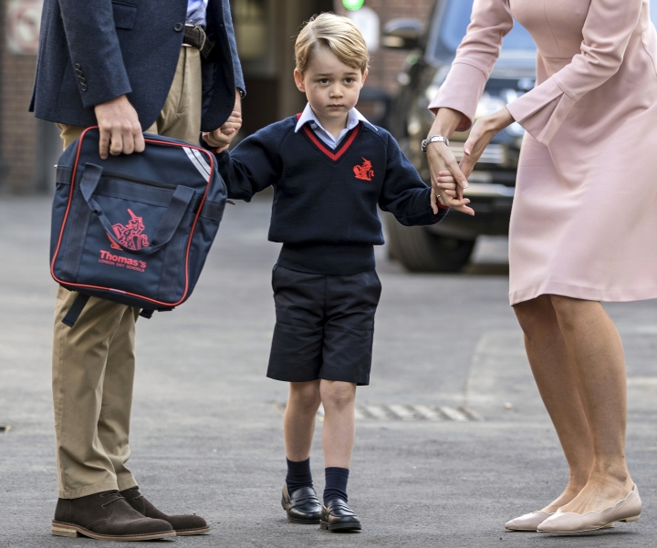 FILE - In this Thursday, Sept. 7, 2017 file photo, Britain's Prince William accompanies Prince George as he is met by Helen Haslem - the head of the lower school on arrival for his first day of school at Thomas's school in Battersea, London. A 31-year-old man has been charged in England with sharing a photo of Prince George and details about his pre-school in a social media post prosecutors allege was meant to help others plan terror attacks, it was announced on Wednesday, Dec. 6, 2017. Prosecutors allege Husnain Rashid put the information about the 4-year-old son of Prince William and the former Kate Middleton on the encrypted platform Telegram. Britain's Sun newspaper reports that Rashid allegedly posted the silhouette of an Islamic State fighter beside George. (Richard Pohle/Pool Photo via AP)