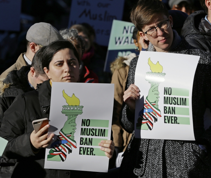 "Mana Rostami-Mouripour, left, and Sara Sluszka, right, both of Seattle, hold signs that read ""No Muslim Ban Ever,"" during a protest, Wednesday, Dec. 6, 2017, outside a federal courthouse in Seattle. The U.S. Supreme Court decision allowing President Donald Trump's third travel ban to take effect has intensified the attention on a legal showdown Wednesday before three judges in Seattle who have been cool to the policy as they hear arguments in Hawaii's challenge to the ban, which restricts travel to the United States by residents of six mostly Muslim countries and has been reviled by critics as discriminatory. (AP Photo/Ted S. Warren)"
