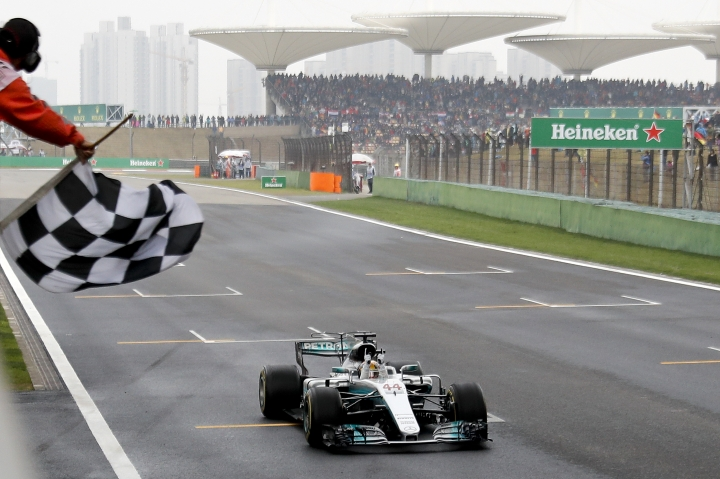 FILE - In this April 9, 2017, file photo, Mercedes driver Lewis Hamilton of Britain gets the checkered flag to win the Chinese Formula One Grand Prix at the Shanghai International Circuit in Shanghai, China. Formula One races in Bahrain and China will swap places early in the season as initially planned following approval of the 2018 F1 calendar on Wednesday, Dec. 6, 2017. (AP Photo/Andy Wong, Pool, File)