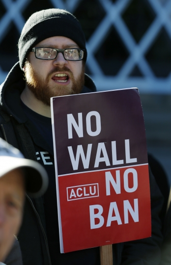 """Eric Buerk, of Seattle, holds a sign that reads """"No Wall No Ban,"""" during a protest, Wednesday, Dec. 6, 2017, outside a federal courthouse in Seattle. The U.S. Supreme Court decision allowing President Donald Trump's third travel ban to take effect has intensified the attention on a legal showdown Wednesday before three judges in Seattle who have been cool to the policy as they hear arguments in Hawaii's challenge to the ban, which restricts travel to the United States by residents of six mostly Muslim countries and has been reviled by critics as discriminatory. (AP Photo/Ted S. Warren)"""