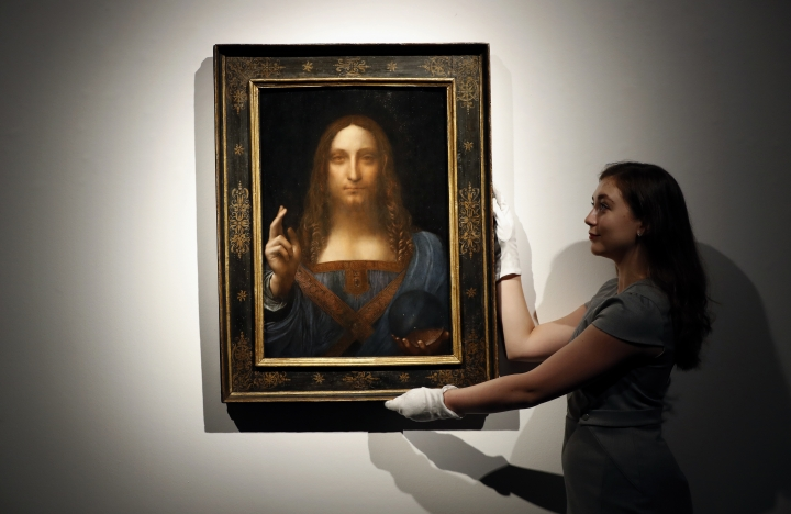"""FILE- In this Oct. 24, 2017 file photo, an employee poses with Leonardo da Vinci's """"Salvator Mundi"""" on display at Christie's auction rooms in London. The rare painting of Christ, which that sold for a record $450 million, is heading to a museum in Abu Dhabi. The newly-opened Louvre Abu Dhabi made the announcement in a tweet on Wednesday, Dec. 6. (AP Photo/Kirsty Wigglesworth, File)"""