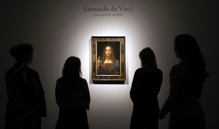 "FILE- In this Oct. 24, 2017, file photo, people gather around Leonardo da Vinci's ""Salvator Mundi"" on display at Christie's auction rooms in London. The rare painting of Christ, which that sold for a record $450 million, is heading to a museum in Abu Dhabi. The newly-opened Louvre Abu Dhabi made the announcement in a tweet on Wednesday, Dec. 6. (AP Photo/Kirsty Wigglesworth, File)"
