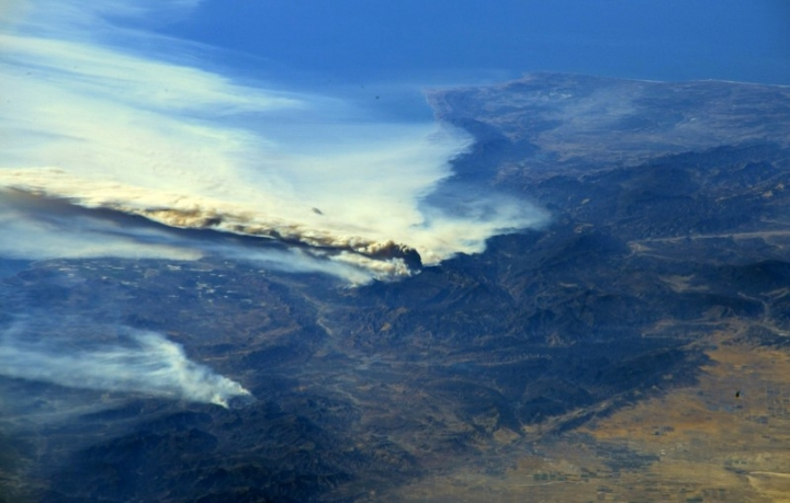 A photo taken from the International Space Station and moved on social media by astronaut Randy Bresnik shows smoke rising from wildfire burning in Southern California, U.S., December 6, 2017.  Courtesy @AstroKomrade/NASA/Handout via REUTERS