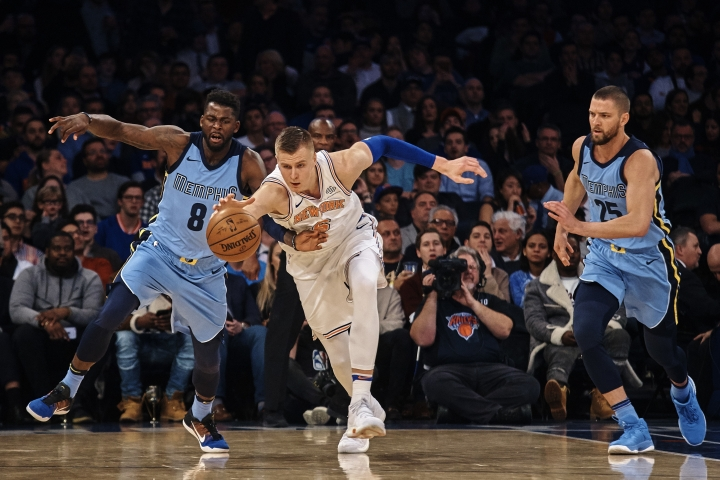 Memphis Grizzlies' James Ennis III (8) competes for the ball with New York Knicks' Kristaps Porzingis, center, during the first half of an NBA basketball game at Madison Square Garden in New York, Wednesday, Dec. 6, 2017. (AP Photo/Andres Kudacki)