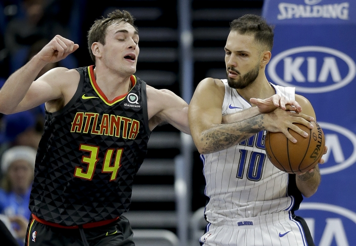 Atlanta Hawks' Tyler Cavanaugh (34) reaches under the arm of Orlando Magic's Evan Fournier (10) as he tries to steal the ball during the first half of an NBA basketball game, Wednesday, Dec. 6, 2017, in Orlando, Fla. (AP Photo/John Raoux)