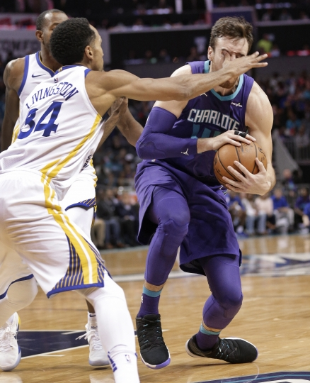 Charlotte Hornets' Frank Kaminsky, right, is poked in the eye by Golden State Warriors' Shaun Livingston (34) during the first half of an NBA basketball game in Charlotte, N.C., Wednesday, Dec. 6, 2017. Kaminsky left the court after injuring his ankle on the play. (AP Photo/Chuck Burton)